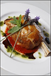 Roasted lamb shank in puff pastry with a fresh herb tomato sauce and mint drizzle